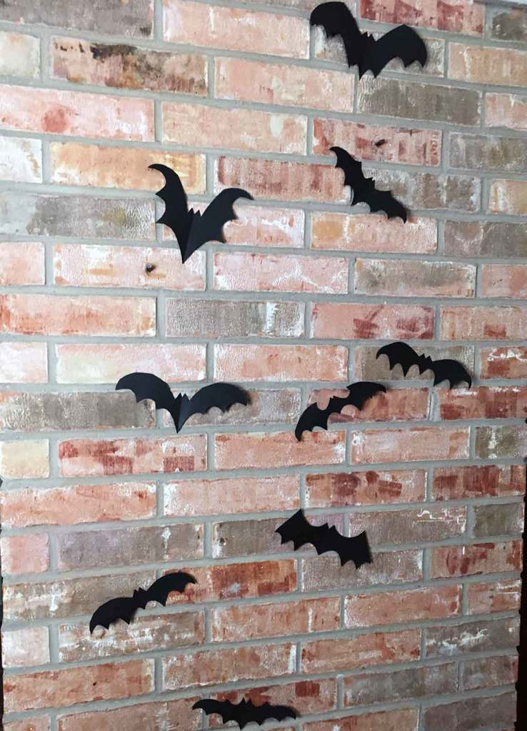 Use masking tape to attach your paper bats to the wall.
