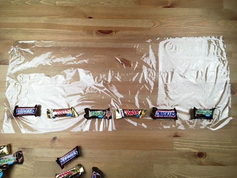 Line up your candy on the saran wrap when making a candy lei for graduation